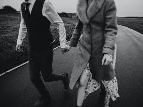 Grayscale Close-up Photo of Couple Holding Hands While Walking Down an Empty Road
