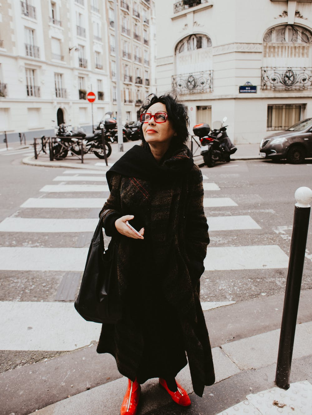 Woman wearing black coat and staring at a building | Photo: Pexels