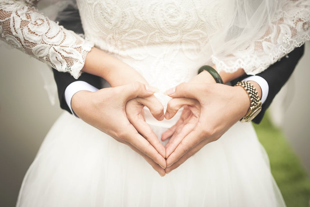 Newly wedded couple making heart shape with hands | Photo: Pexels