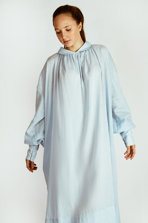 Photo of Woman in White Long-sleeved Night Dress Posing While Looking Down In Front of White Background