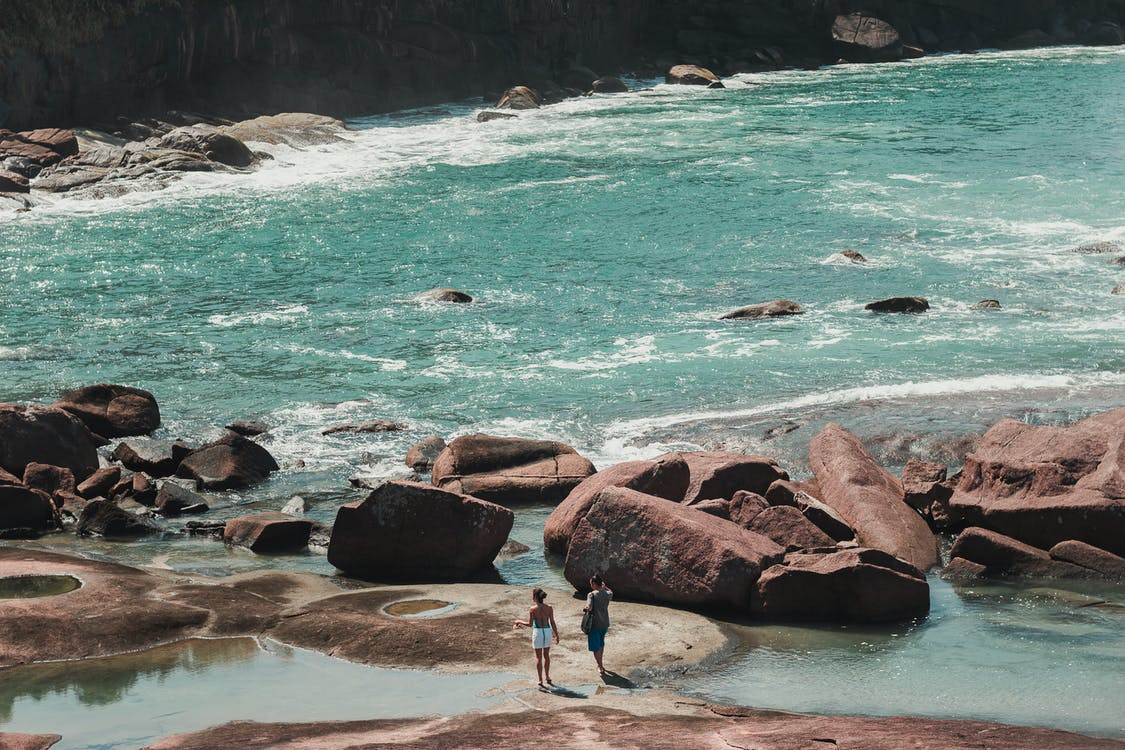 Photo of People On Rocky Shore