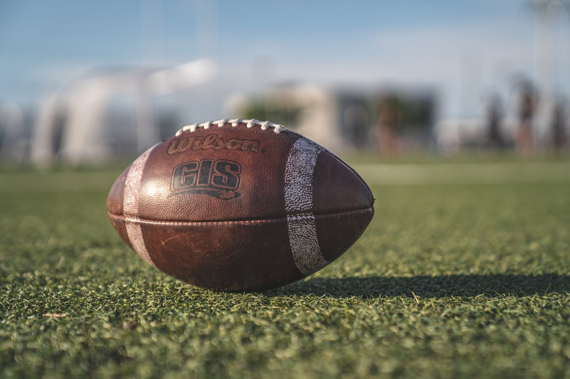Selective Focus Close-up Photo of Brown Wilson Pigskin Football on Green Grass