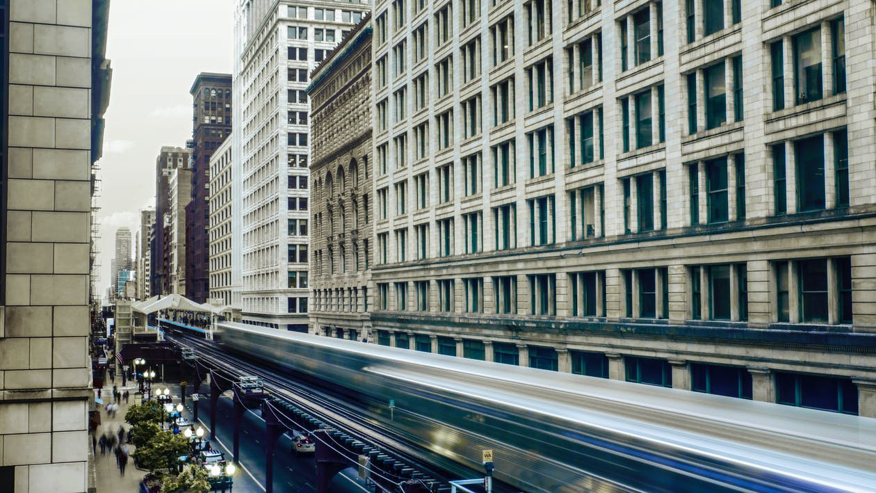 Time Lapse Photo of White Train Passing by Buildings