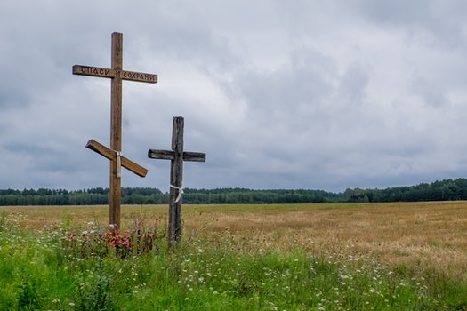 View of Cross on Field Against Cloudy Sky