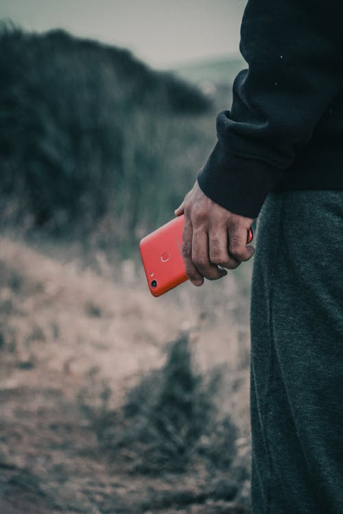 Selective Focus Photo of Man's Hand Holding Red Smartphone