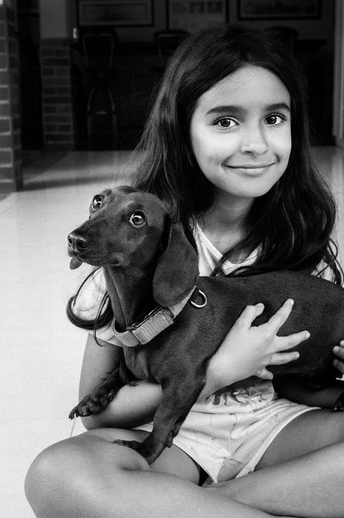 Grayscale Photography Of Smiling Girl Carrying A Dog