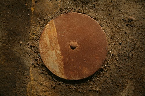 Round Brown Metal Machine Part on Brown Surface