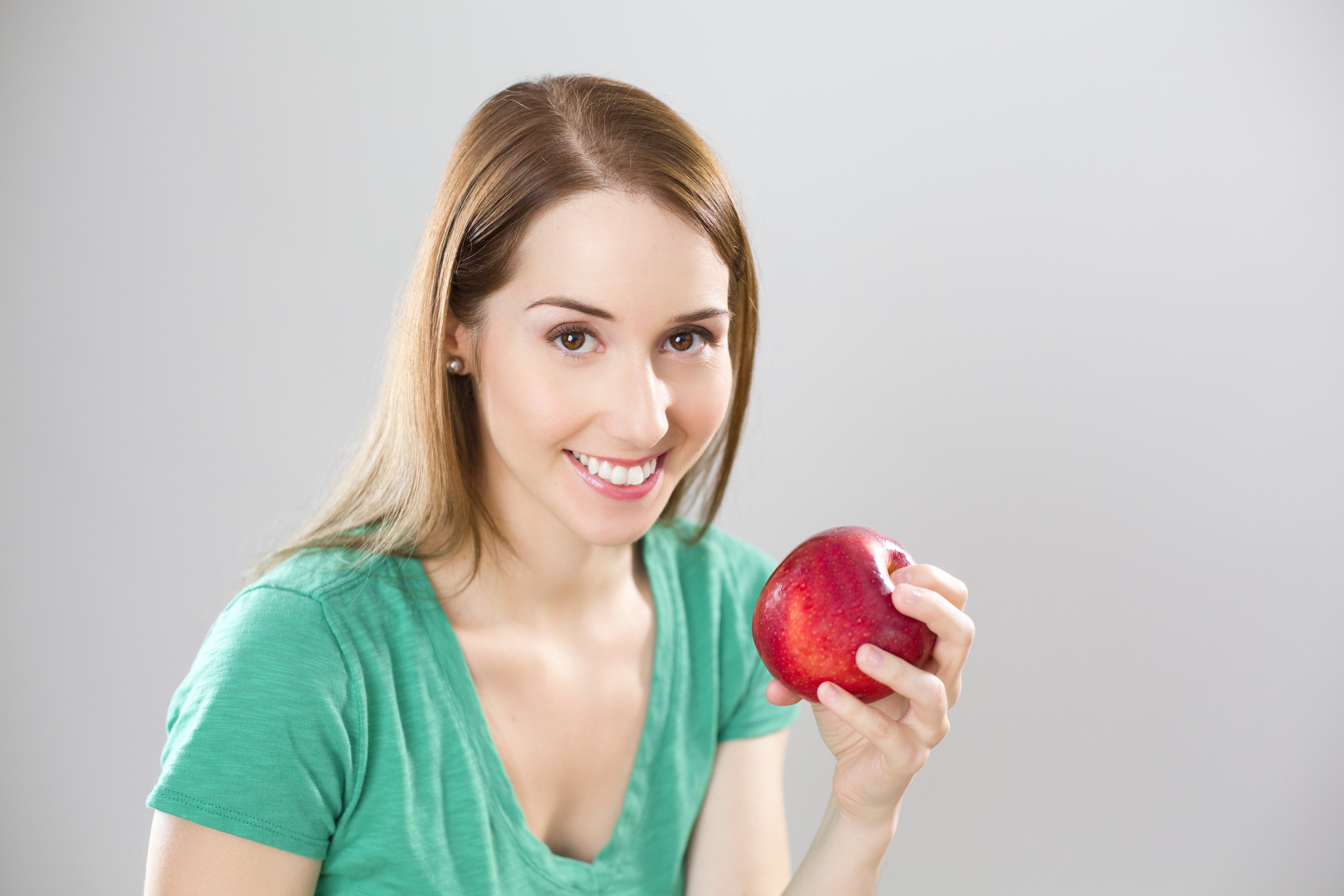 Portrait of Young Woman Eating Fruit Against White Background