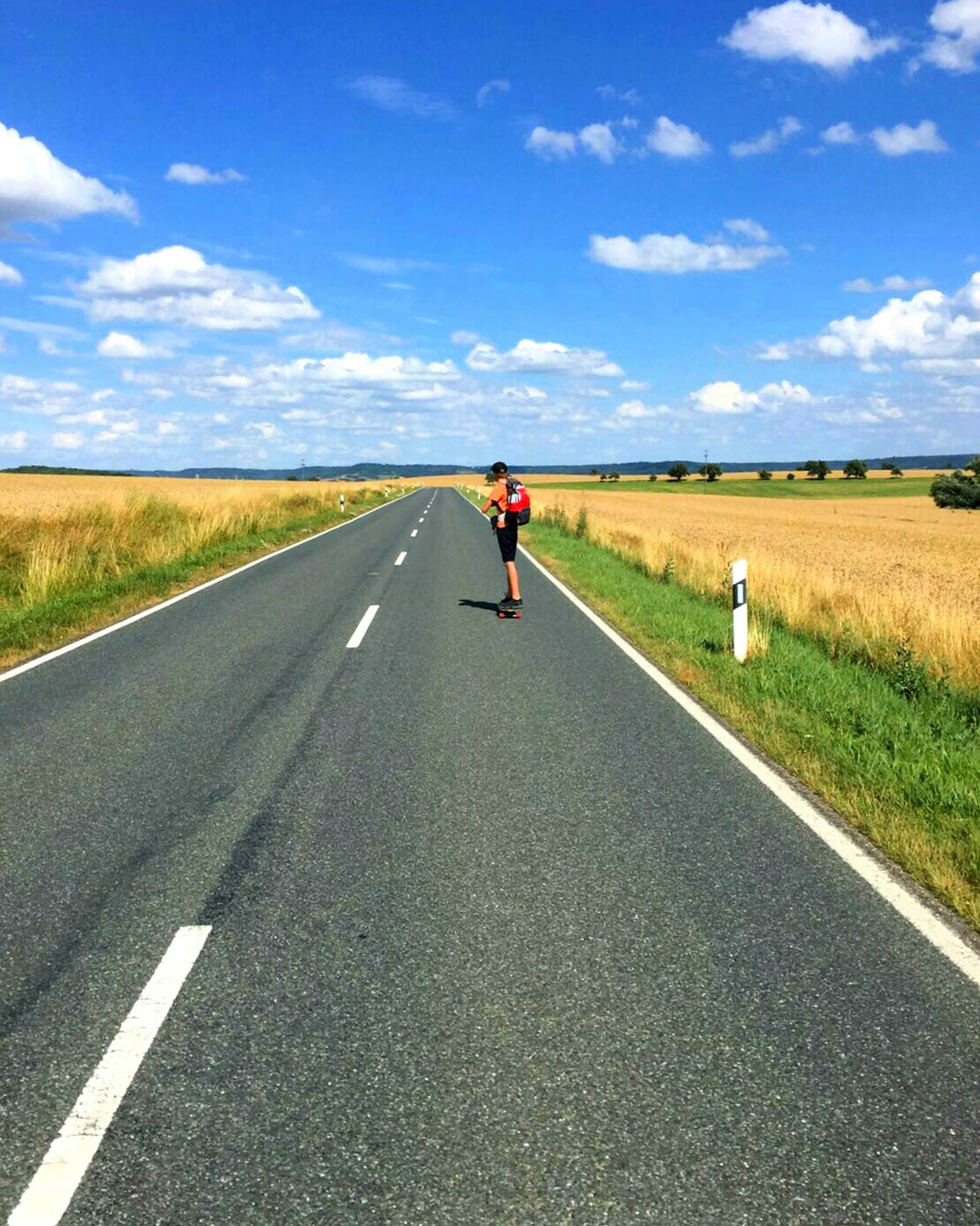 Man Cycling on Road Against Sky