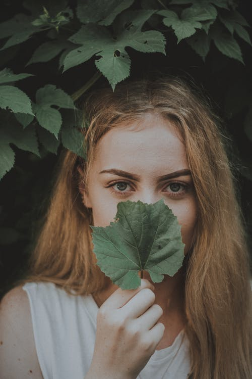 Woman Covering Her Mouth And Nose With Green Leaf