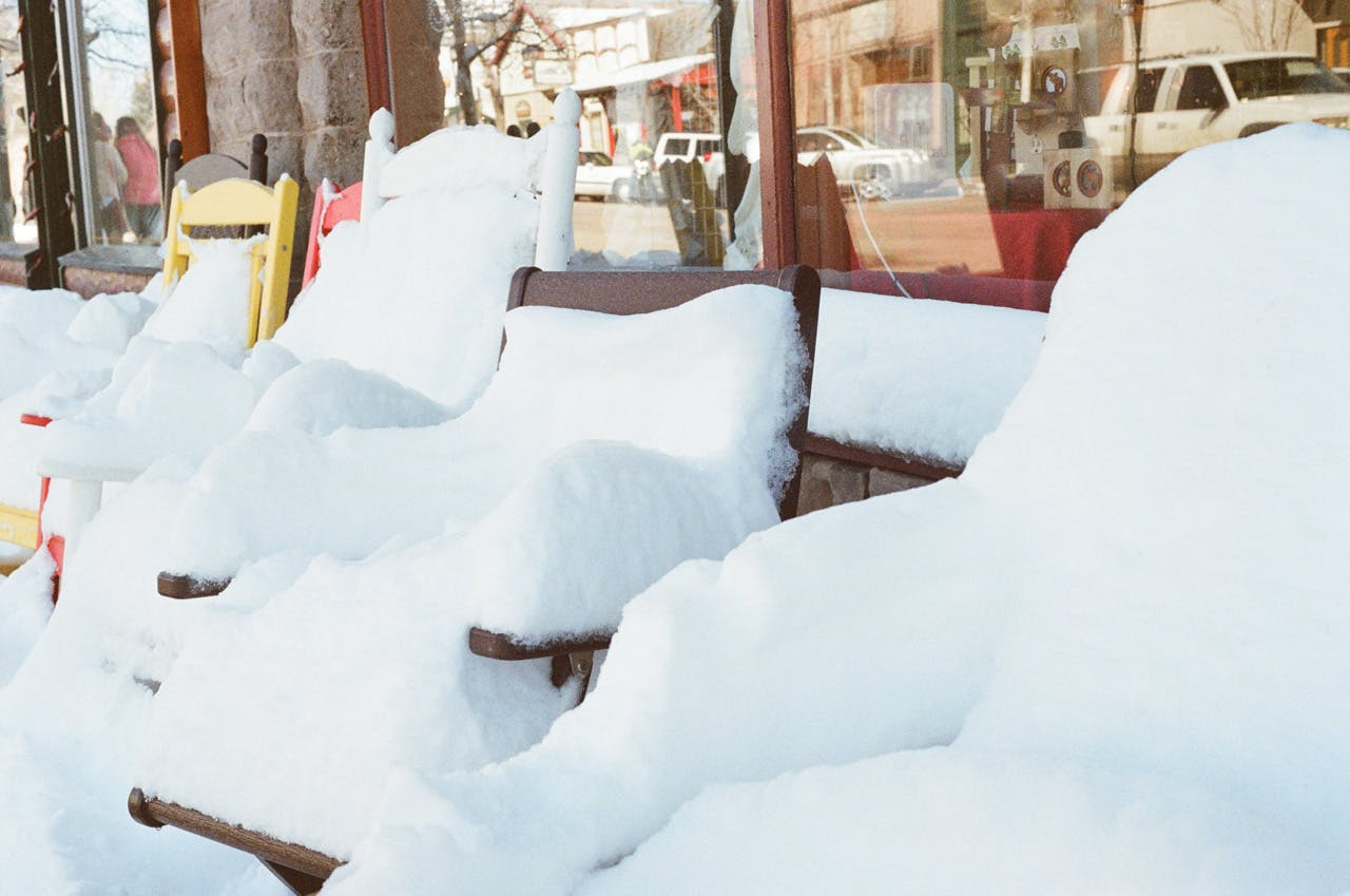 Snow Coated Chairs Beside Clear Glass Storefront
