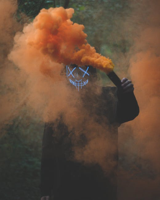 Person wearing mask holding colored smoke bomb