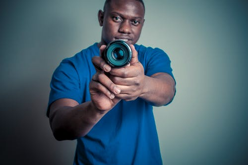 Man In Blue Shirt Holding Camera Lens