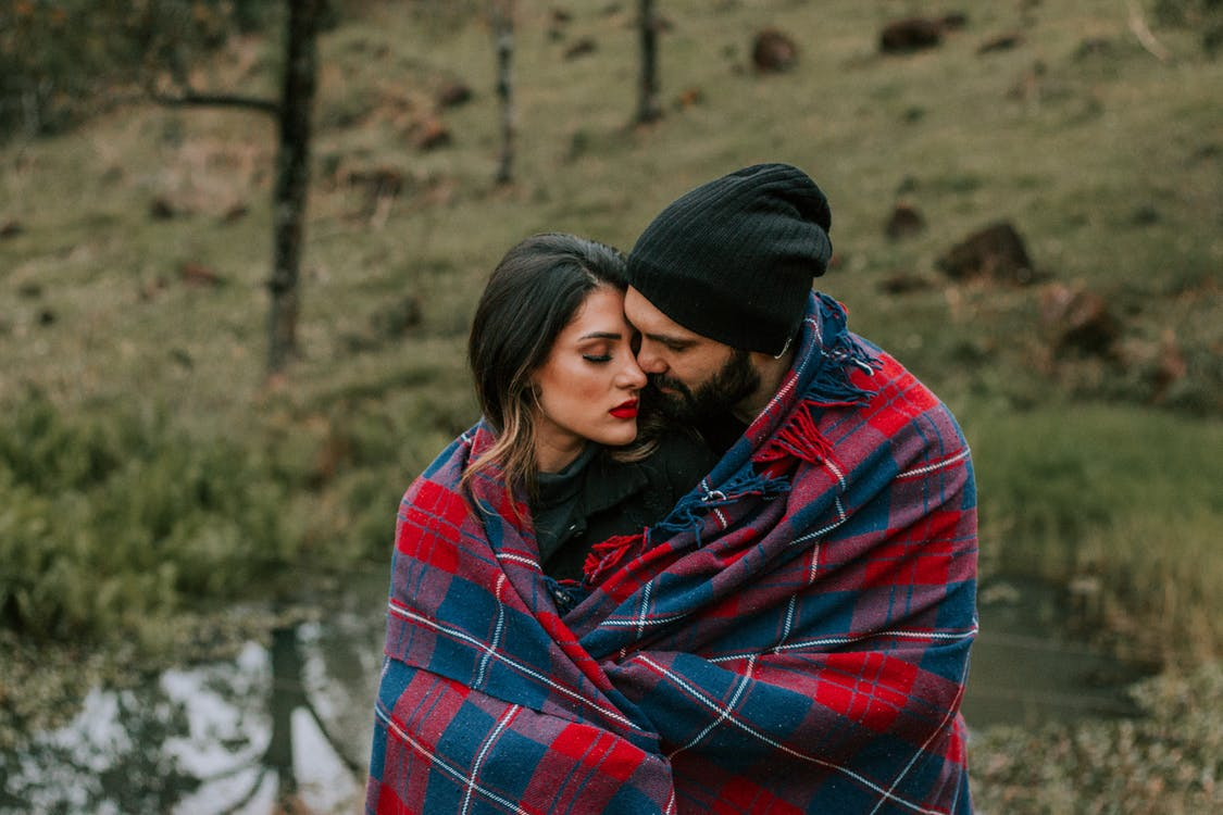 Photo of Hugging Couple Covered in Red and Black Blanket Outdoors