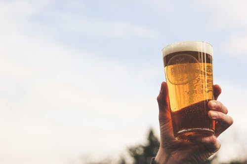 Close-Up Photo of Person Holding Glass of Beer