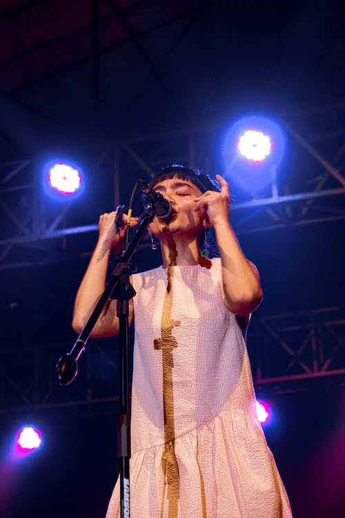 Girl Wearing White Sleeveless Dress Performing On Stage