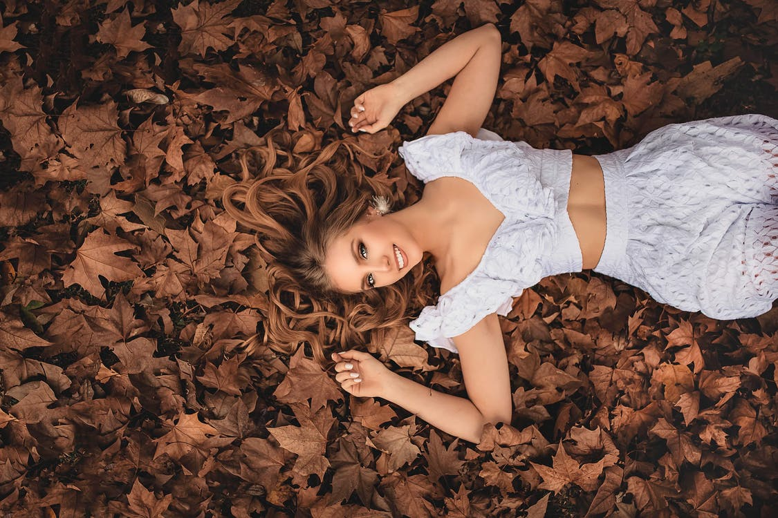 Woman In White Crop Top aAd Shorts Lying On Brown Dry Leaves