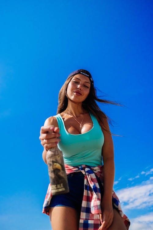 Бесплатное стоковое фото с брюнетка, бутылка пива, выражение лица, голубое небо