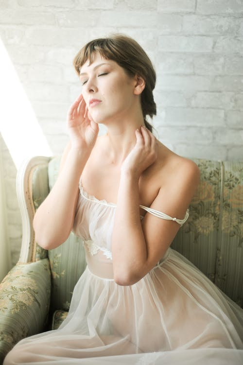 Photo of Woman in White Sheer Gown Sitting on Sofa Posing With Her Eyes Closed