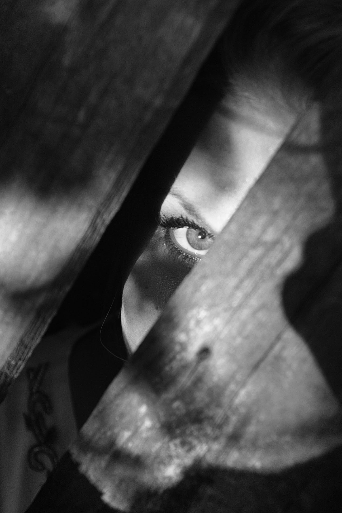 Grayscale Photo of Woman Peeking on Planks