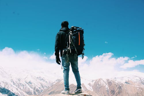 Photo of Man Standing On Top Of Mountain