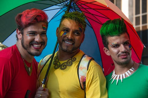 Three Man Under Multi-coloured Umbrella