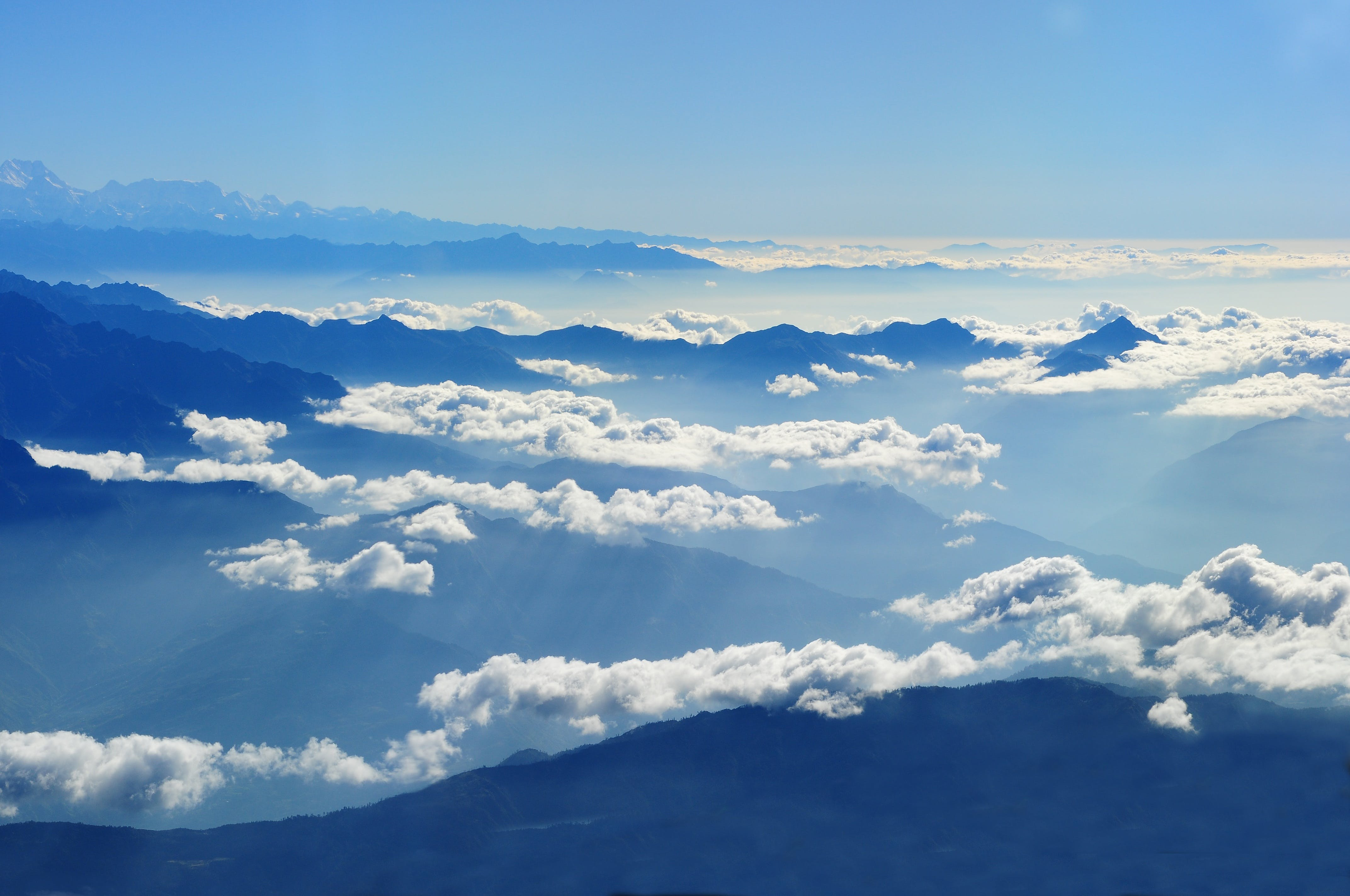 Scenic View of Clouds over Mountains Against Blue Sky