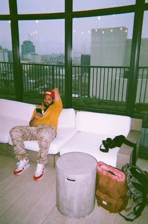 Casual guy with phone on lobby sofa