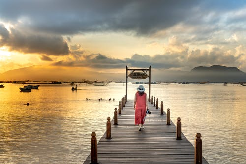 Back View Photo of Woman in Pink Outfit and Sun Hat Walking on Wooden Dock Over Lake While Carrying a Dslr Camera