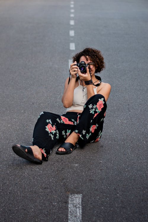 Photo of a Woman Sitting on Road Holding Camera