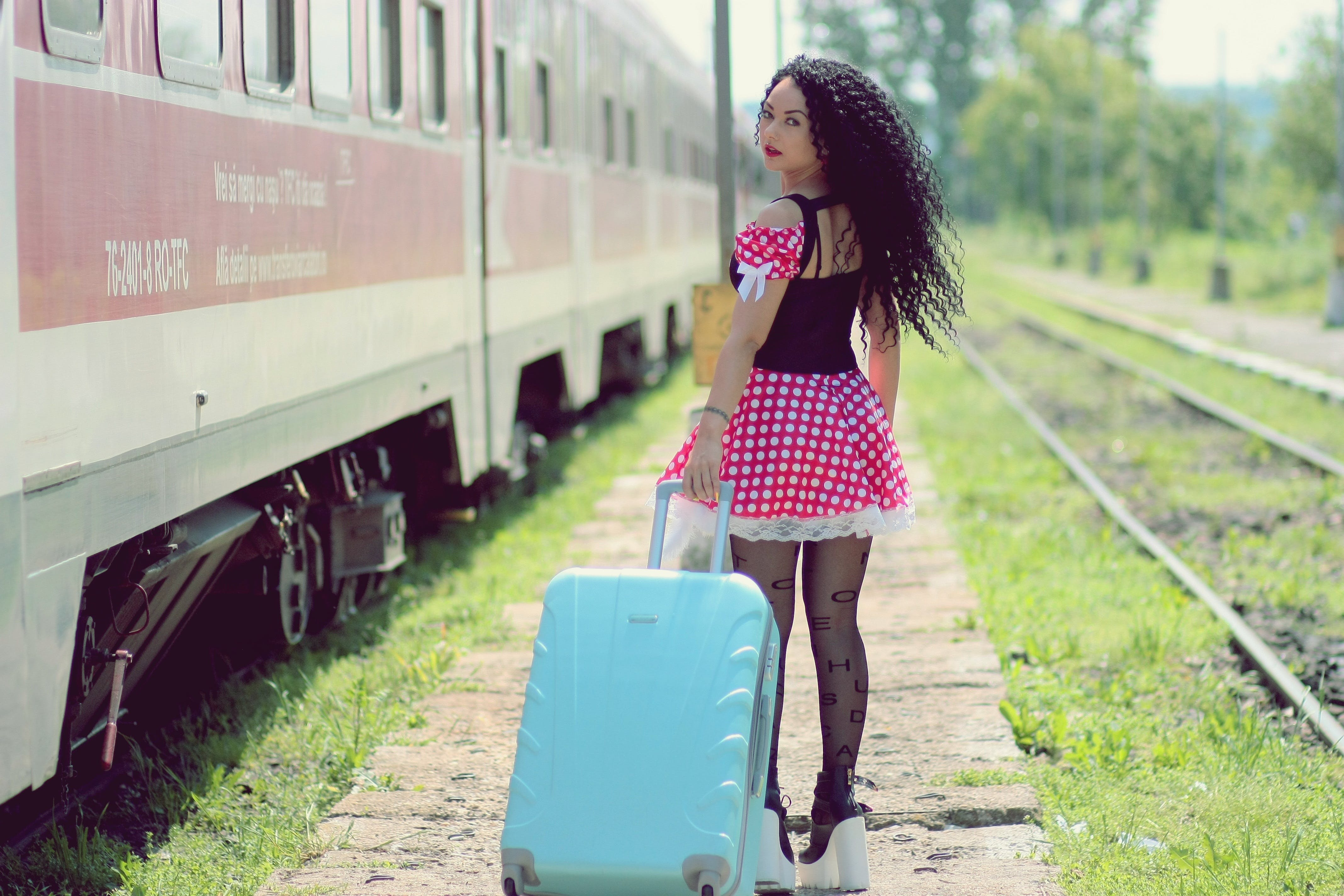 Young Woman With Luggage Standing on Train in City