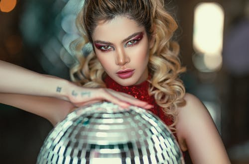 Photo of a Woman Holding Disco Ball
