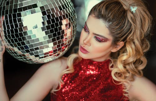 Photo of a Woman in Red Glitter Halter Top Holding Disco Ball