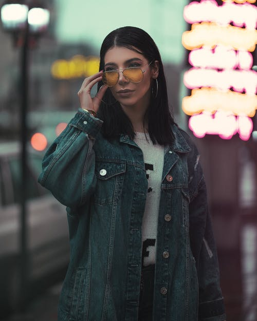 Selective Focus Photo of Woman in Denim Jacket and Sunglasses Posing