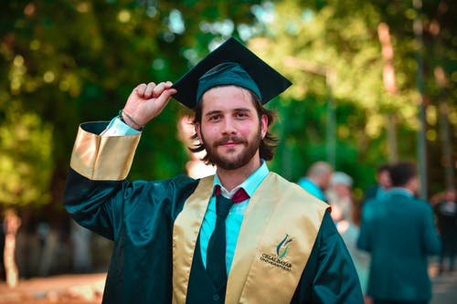 Photo of Smiling Man in Gold and Black Academic Dress Posing