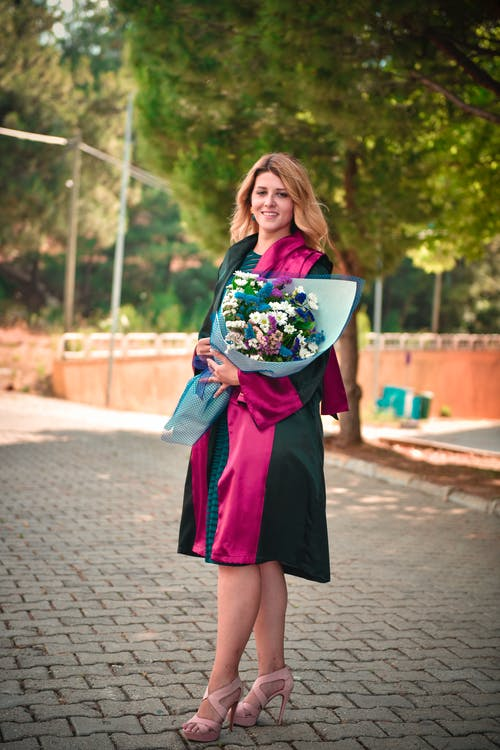 Smiling Woman in Black and Pink Academic Dress Posing on Concrete Pavement Holding a Bouquet of Flowers
