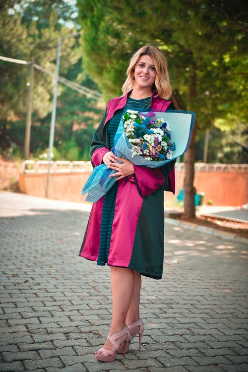 Photo of Smiling Woman in Black and Pink Graduation Gown Posing While Carrying Bouquet of Flowers