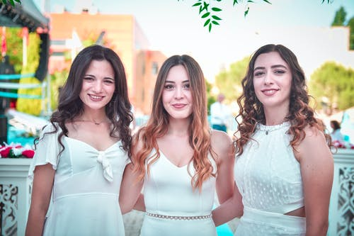 Photo of Three Smiling Women in White Dress Standing Together