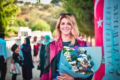 Photo of Smiling Woman in Pink and Black Academic Gown Posing While Holding Bouquet of Flowers with a Crowd of People in the Background