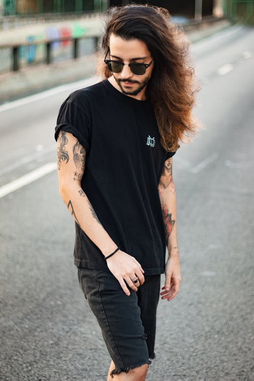 Photo of Tattooed Man in Black T-shirt, Sunglasses, and Black Denim Shorts Posing in Middle of Road While Looking Down