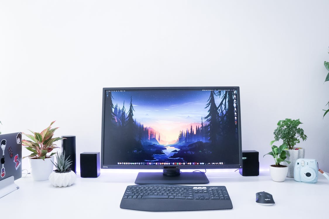 Turned-on Black Flat Screen Computer Monitor and Keyboard