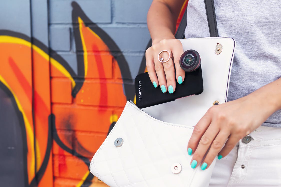Photo of Person Carrying Bag While Holding Smartphone