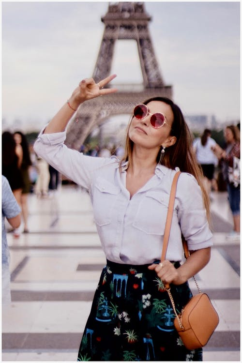 Photo of a Woman in White Long-sleeved Shirt Standing Near Eiffel Tower