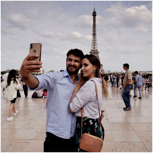 Photo of a Man and Woman Taking Selfie With Background of Eiffel Tower of Paris