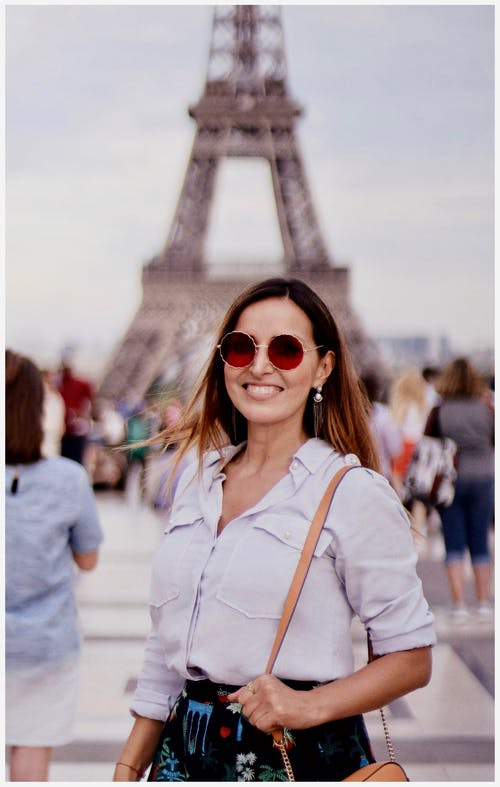 Selective Focus Photo of Smiling Woman Posing With a Crowd of People and The Eiffel Tower in the Background
