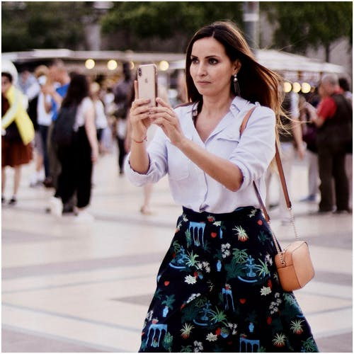 Photo of a Woman Taking a Photo Using Her Cellphone
