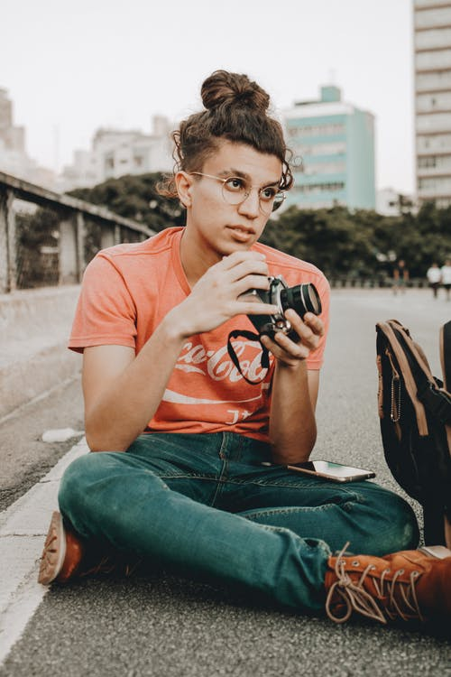 Man Holding Black Dslr Camera