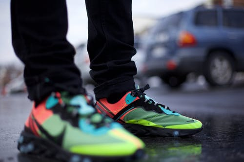 Selective Focus Photo of Person Wearing Sneakers