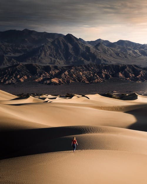 Photo of a Woman Walking on Desert