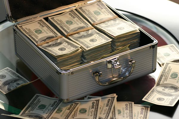 A photgraph of a briefcase full of $100 bills on a glass table.